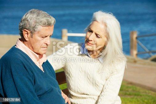 istock Mature Woman Comforting Husband on Sandy Beach 159125184