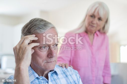 874789476istockphoto Mature Woman Comforting Man With Depression At Home 827639744