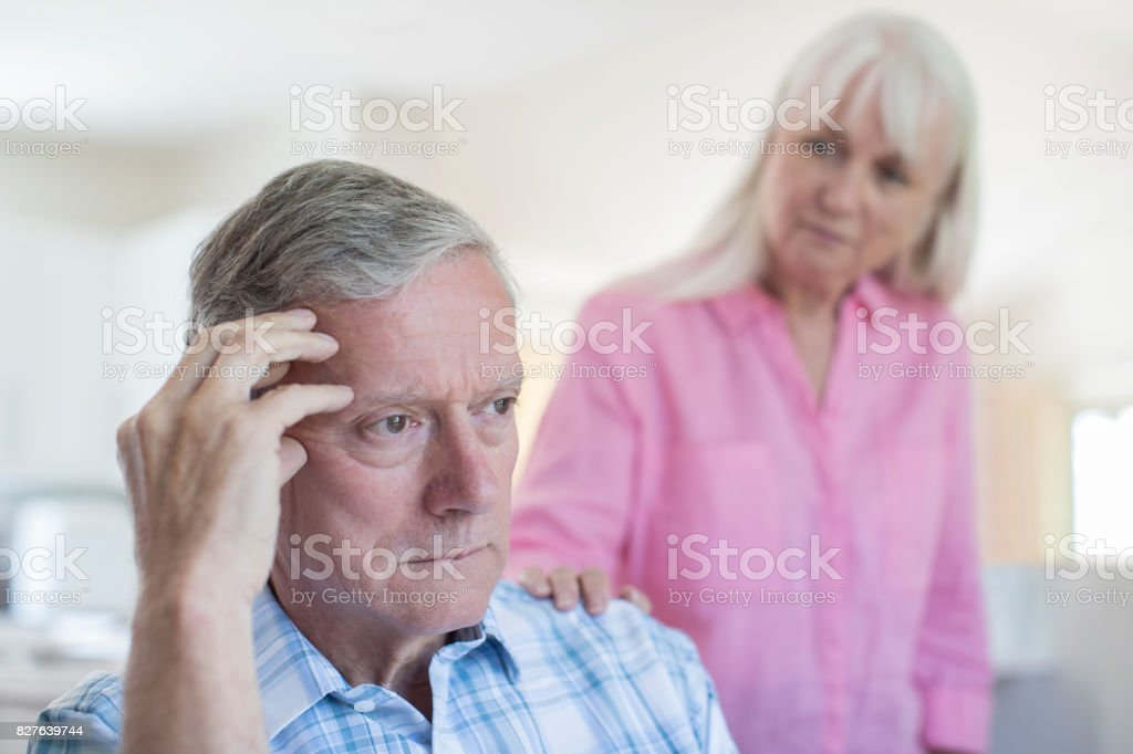 Mature Woman Comforting Man With Depression At Home stock photo