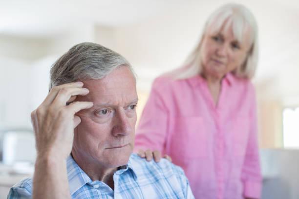 rijpe vrouw troost man met depressie thuis - dementia stockfoto's en -beelden