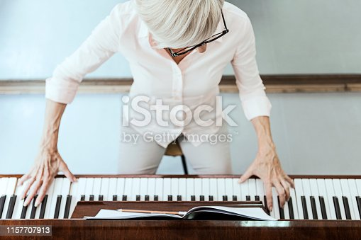 Mature lady playing piano at home