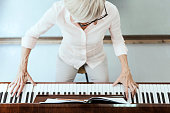 Mature lady playing piano at home