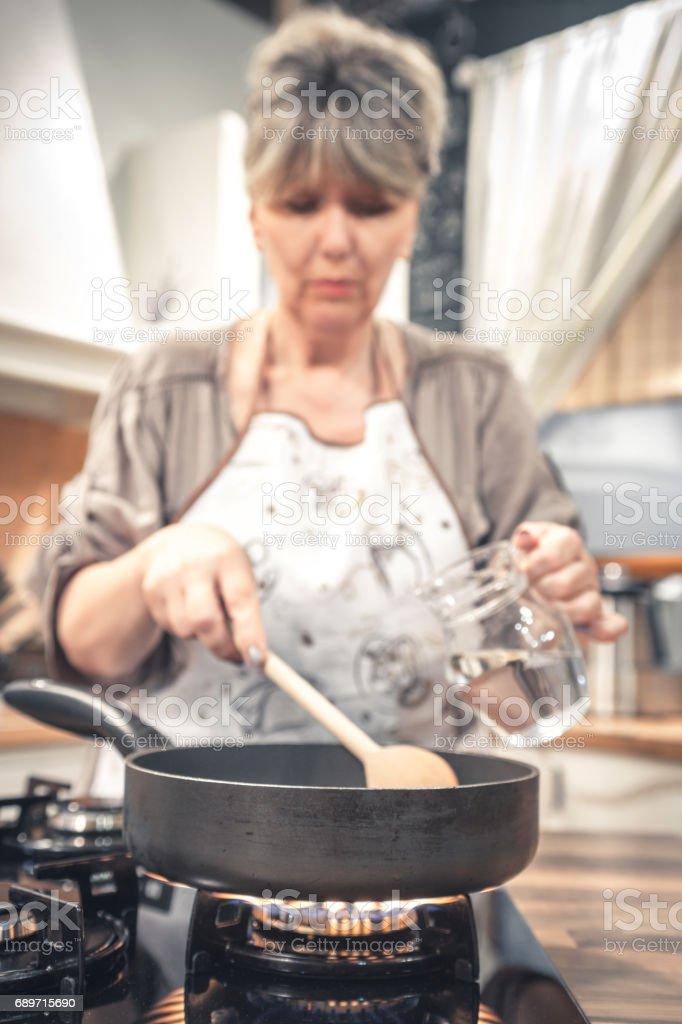 Reife Frau Kochen Auf Gasherd Stock Fotografie Und Mehr Bilder Von