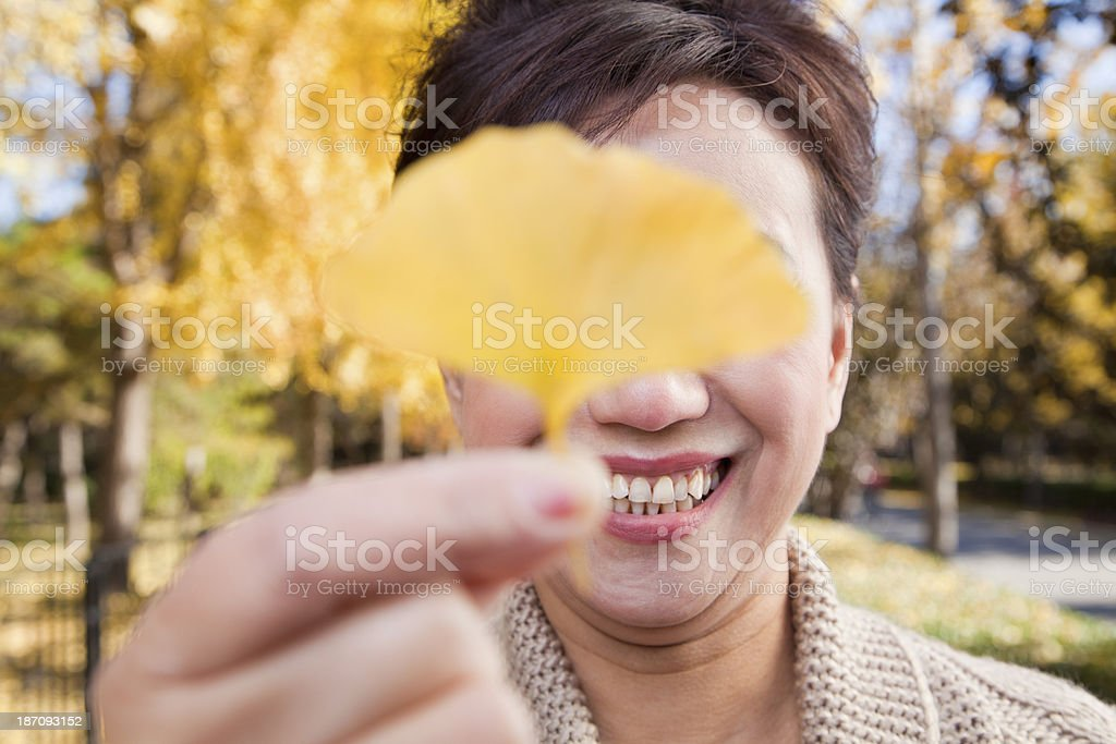 Mature Woman Covering Her Eyes with Yellow Ginkgo Leaf royalty-free stock photo