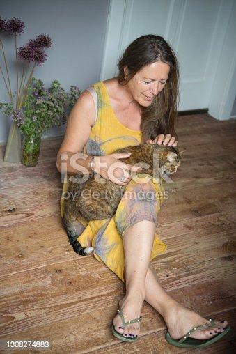 Mature Woman Cuddling with her Feline Friend