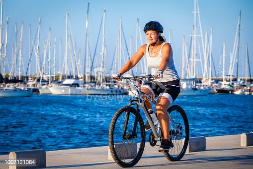 Three quarters front view of a mature woman cycling a mountain bike near sea water on pier in marina. The woman is wearing sport clothes Predominant color is blue. Copy space available for text and/or logo. DSRL outdoors photo taken with Canon EOS 5D Mk II and Canon EF 24-105mm f/4L IS USM Wide Angle Zoom Lens