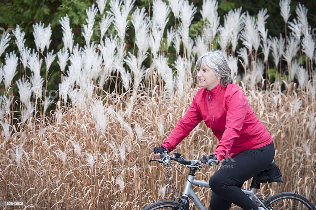 Mature woman cycling royalty-free stock photo