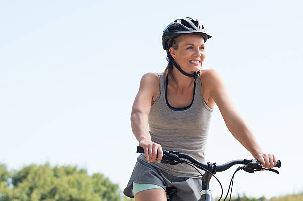 mature woman cycling - mid adult women stock pictures, royalty-free photos & images