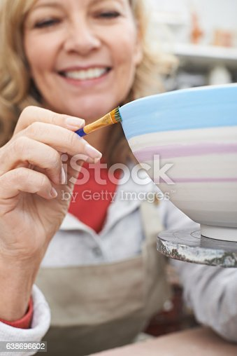 istock Mature Woman Decorating Bowl In Pottery Class 638696602