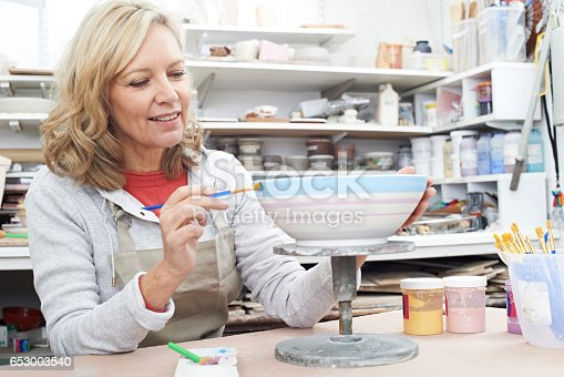 istock Mature Woman Decorating Bowl In Pottery Class 653003540