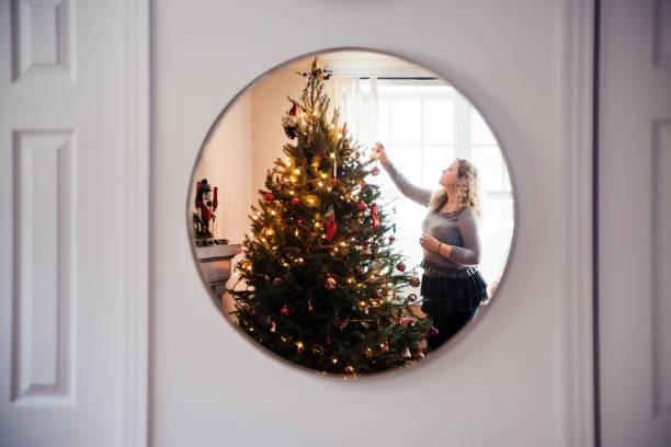 reife frau schmücken weihnachtsbaum zu hause. - kanada rundreise stock-fotos und bilder