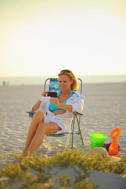 donna matura versando verificare con il telefono cellulare - holiday and invoice family foto e immagini stock