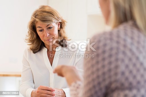 istock Mature Woman Discussing Problems With Counselor 860923864