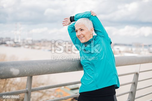 1057638814 istock photo Mature woman doing back exercise 958918660