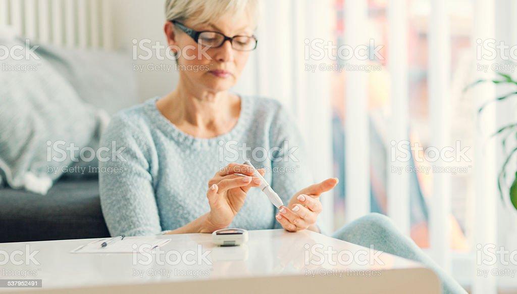 Reife Frau beim Blutzuckermessung wie zu Hause fühlen. – Foto