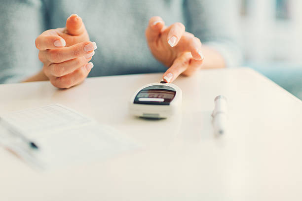 Mature Woman Doing Blood Sugar Test at home. Mature woman doing blood sugar test at home in a living room. Selective focus to her finger. endocrine system stock pictures, royalty-free photos & images