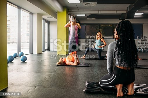 1195045259istockphoto Mature Woman Doing Perfect Candlestick Exercise In Gym 1195051139