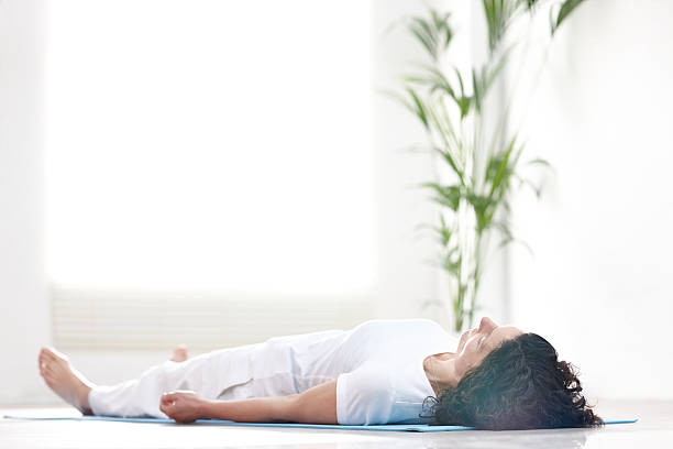 Mature woman doing savasana Mature woman lying on a yoga mat and relaxing after workout - Savasana lying on back stock pictures, royalty-free photos & images