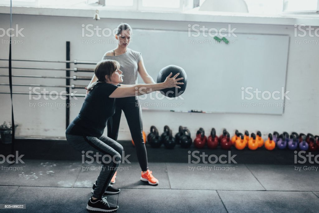 Mature Woman Doing Squats While Holding Medicine Ball Stock Photo