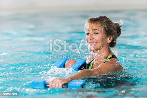 istock Mature woman doing water aerobics with dumbbells 533517881