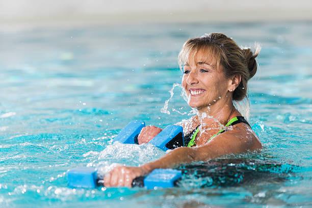 Donna matura facendo acqua aerobica con manubri - foto stock