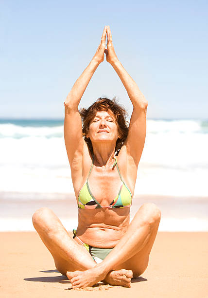 Mature Woman Doing Yoga and Relaxing on the Beach Mature Woman Doing Yoga and Relaxing on the Beach middle aged women in bikinis stock pictures, royalty-free photos & images