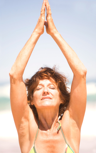 479652946 istock photo Mature Woman Doing Yoga and Relaxing on the Beach 182247072