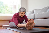 istock Mature woman doing yoga exercise at home 1044154482