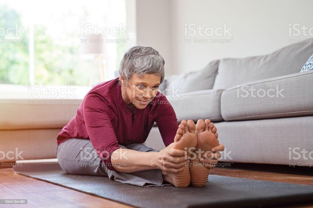 Femme mature, faire des exercices d'yoga à la maison - Photo