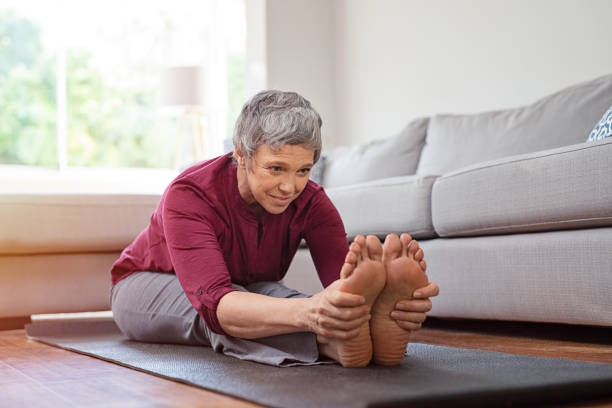 Mature woman doing yoga exercise at home stock photo