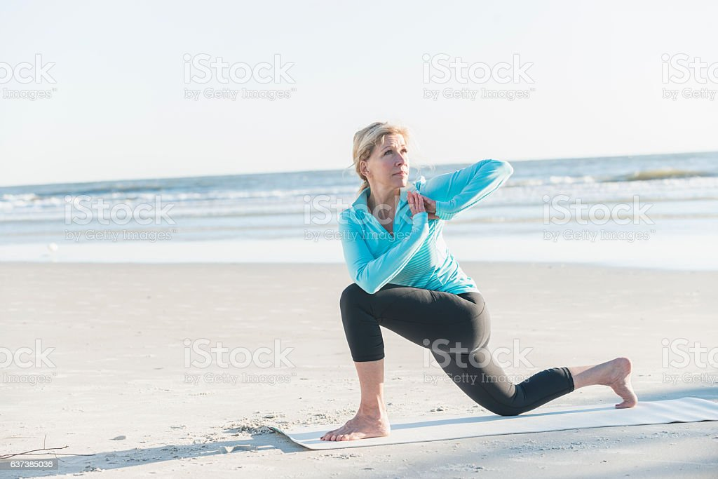 Mature woman doing yoga exercises on beach stock photo