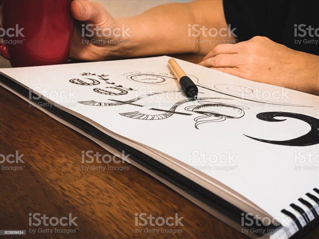 Mature Woman Doodles Coffee Art While Having. A Cup Of Coffee stock photo