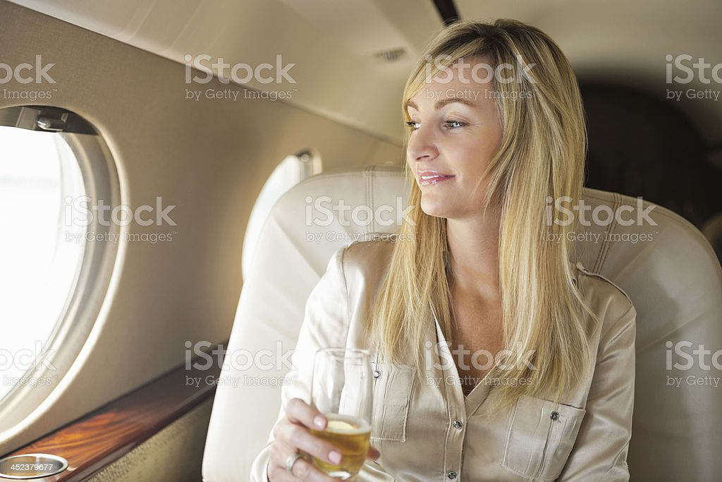 Mature woman drinking champagne on board luxurious private jet stock photo