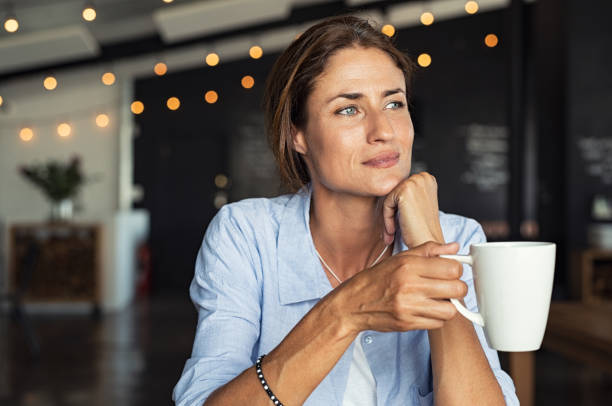 mature woman drinking coffee - deliberation stock pictures, royalty-free photos & images