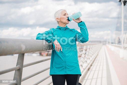 1057638814 istock photo Mature woman drinking water 958918692