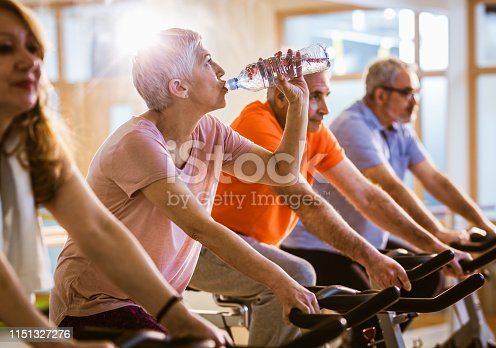Active seniors having cycling class in a health club. Focus is on thirsty woman refreshing her self with water.