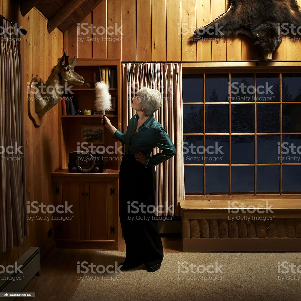 Mature woman dusting with feather duster royalty free stockfoto