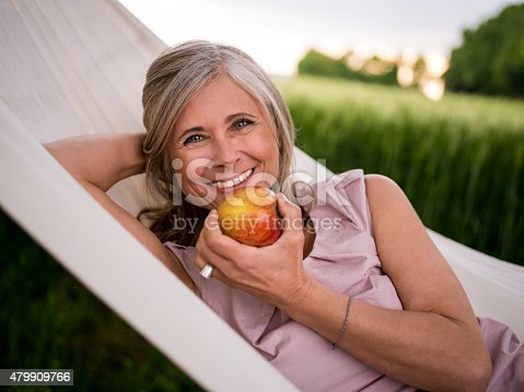 Healthy mature woman relaxing in a hammock in a park and eating a fresh apple