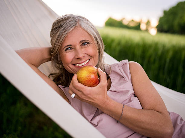 mature woman eating a fresh apple while relaxing outdoors - ripe stock photos and pictures