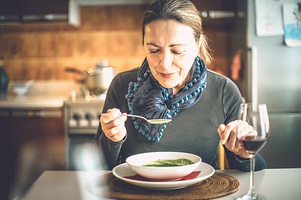 reife frau essen suppe - spinatsuppe stock-fotos und bilder