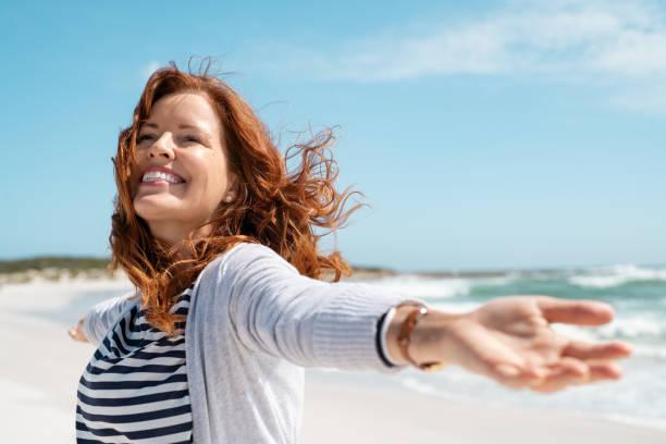 成熟的女人享受微風在沙灘上 - 幸福 個照片及圖片檔