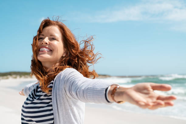 Mature woman enjoy breeze at beach stock photo