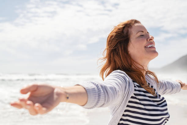 Mature woman enjoy summer beach Happy redhead woman relaxing with arms outstretched at beach on a bright morning with eyes closed. Beautiful middle aged woman felling free at sea. Smiling cheerful mid woman relaxing at the seaside with copy space. carefree stock pictures, royalty-free photos & images