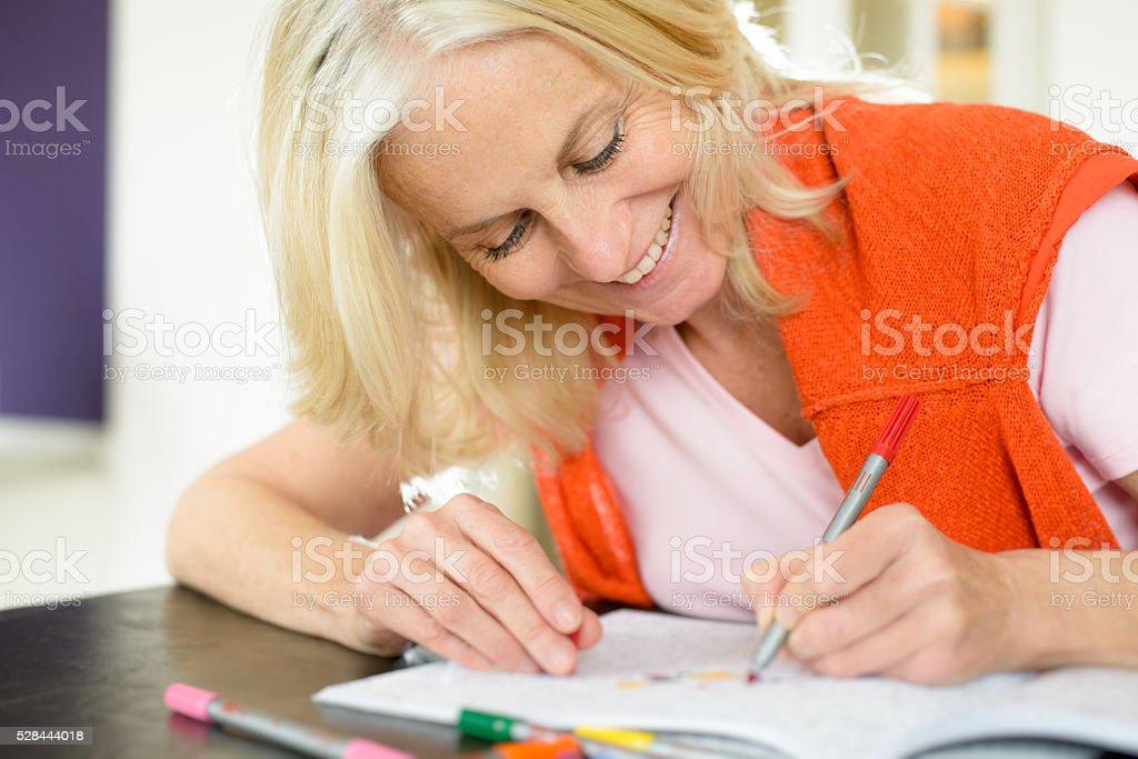 Mature Woman Enjoying Adult Colouring Book stock photo