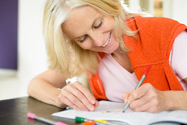 Mature Woman Enjoying Adult Colouring Book stock photo