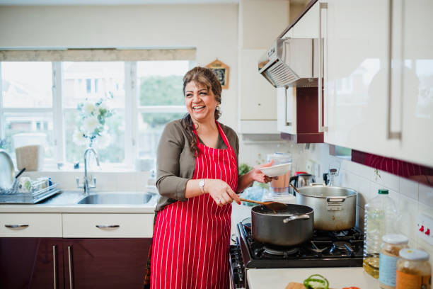 mature woman enjoying cooking at home - woman cooking stock pictures, royalty-free photos & images