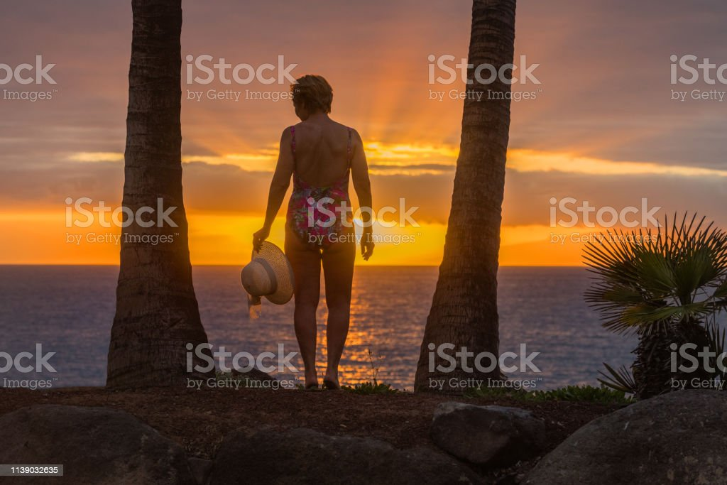 A mature woman enjoys in the sunset under the palm trees,las...