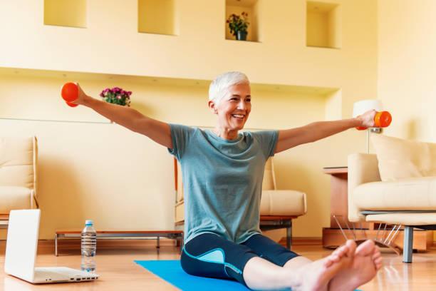 Exercice mûr de femme à la maison. Verticale de femme aînée soulevant des haltères. Femme aîné heureux effectuant la formation de forme physique avec des haltères - Photo