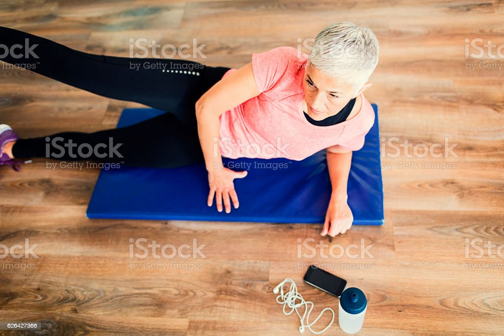 Mature Woman Exercising In Gym. stock photo