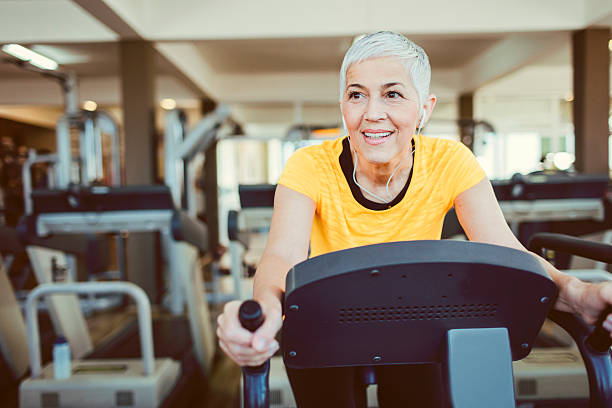 mature woman exercising in gym. - relaxation exercise stock photos and pictures